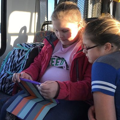 Two girls riding the Friendly Rider playing on an ipad.